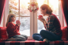 Mother and her daughter enjoying hot tea. Merry Christmas and happy holidays! Happy loving family sitting by the window. Room decorated on Christmas. Pretty Stock Photography