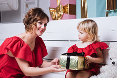 Mother and her daughter exchanging Christmas gifts stock photo
