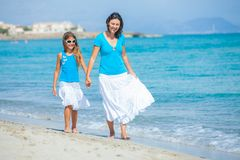 Mother and her daughter having fun on beach Stock Images