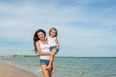 Mother and her daughter  having fun on the beach Stock Image