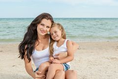 Mother and her daughter  having fun on the beach Stock Photos