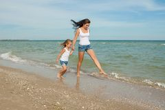 Mother and her daughter  having fun on the beach Royalty Free Stock Photo