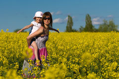 Mother and her daughter having fun at the colza fi Royalty Free Stock Photo