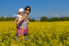 Mother and her daughter having fun at the colza fi Stock Images