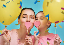 Mother and her daughter are having fun. Funny family on a background of bright blue wall. Mother and her daughter girl are having fun with balloons and confetti Royalty Free Stock Photography
