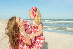 Mother and her daughter  having fun playing on the beach Stock Photo