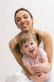 Mother and her daughter having fun and showing tongue Stock Image