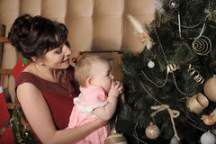 Mother with her daughter in her arms near the Christmas tree Royalty Free Stock Image
