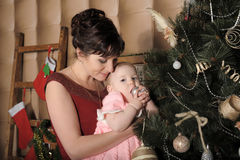 Mother with her daughter in her arms near the Christmas tree Royalty Free Stock Photo