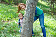 Mother with her daughter hiding behind a tree Stock Image