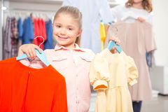 Mother and her daughter holding hangers with Royalty Free Stock Image