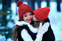 Mother with her daughter kissing outside in winter nature. Royalty Free Stock Photo