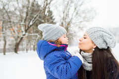 Mother with her daughter kissing outside in winter nature Royalty Free Stock Photo