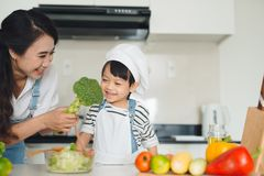 Mother with her daughter in the kitchen cooking together Royalty Free Stock Photography
