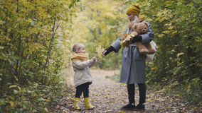 Mother and her daughter little girl walking in a autumn park - playing with Teddy Bear Stock Photo