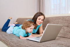Mother and her daughter looking at laptop at home Stock Image