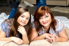 Mother with her daughter lying on the bed. Mother with her daughter lying on the bed and smiling Stock Photos