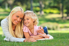 Mother with her daughter lying down outside Stock Photography
