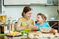 Mother with her daughter makes  fish meatballs in home Royalty Free Stock Image