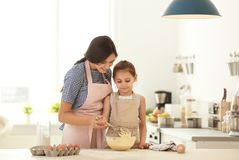 Mother and her daughter making dough at table. In kitchen royalty free stock photo