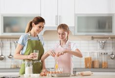 Mother and her daughter making dough at table. In kitchen royalty free stock images