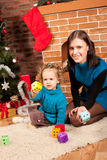 Mother and her daughter near Christmas tree Royalty Free Stock Image