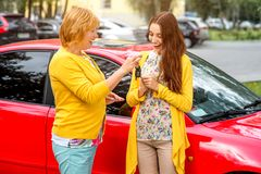 Mother with her daughter near red car Royalty Free Stock Image