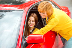 Mother with her daughter near red car Stock Photos