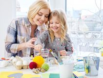 Mother and her daughter painting and decorating easter eggs. Cheerful mother and her daughter painting and decorating easter eggs Stock Photography