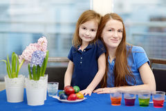 Mother and her daughter painting Easter eggs Stock Photos