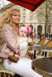Mother and her daughter in Parisian street cafe. Beautiful young mother and her baby daughter in a Parisian street cafe stock photos