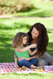 Mother and her daughter picnicking Stock Photos