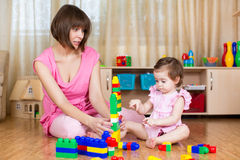 Mother and her daughter play with toys at home Stock Photography