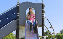 Mother with her daughter on playground. Sunny day Stock Photo