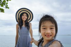 Mother and her daughter playing on beach stock image
