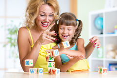 Mother and her daughter playing with cubes Stock Photography