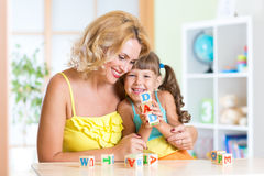 Mother and her daughter playing with cubes Stock Photos