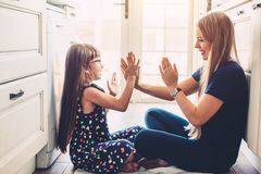 Mom playing with daughter on the kitchen flloor royalty free stock photos