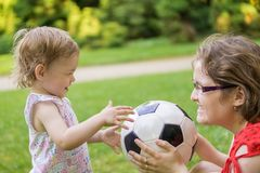 Mother and her daughter are playing with football ball in park royalty free stock images