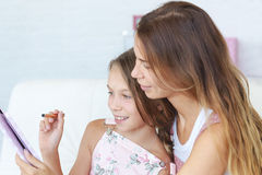 Mother with her daughter playing ipad Royalty Free Stock Photos