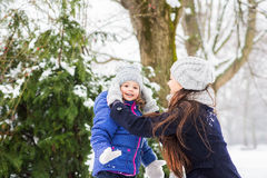 Mother with her daughter playing outside in winter nature Stock Photos