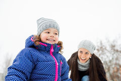 Mother with her daughter playing outside in winter nature Royalty Free Stock Images