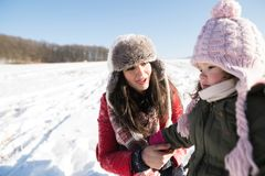 Mother with her daughter, playing in the snow. Royalty Free Stock Photography