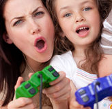 Mother and her daughter playing video games. Excited mother and her daughter playing video games at home Stock Photos