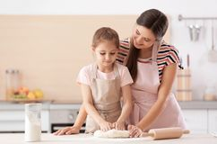 Mother and her daughter preparing dough at table in kitchen. Mother and her cute daughter preparing dough at table in kitchen stock photo