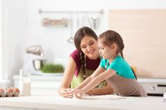 Mother and her daughter preparing dough at table in kitchen. Mother and her cute daughter preparing dough at table in kitchen stock image