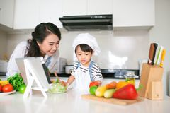 Mother with her daughter preparing lunch in the kitchen and enjoying together stock image
