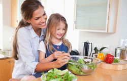 Mother and her daughter preparing a salad Stock Photos