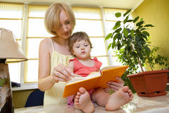 Mother with her daughter reading book Stock Photography