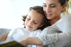 Mother with her daughter reading book Stock Photos